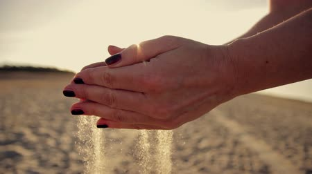 areias : Female hand scatter the sand at  sunset