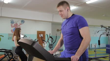 paunchy : Young man and woman instructor working out on a treadmill in a fitness club