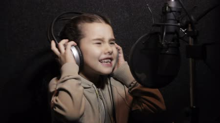 rockstar : Stylish young girl singing with a microphone in music studio Stock Footage