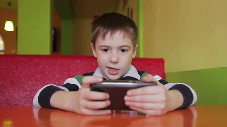 boyish : boy in the cafe playing with a smartphone and sends an SMS to a friend
