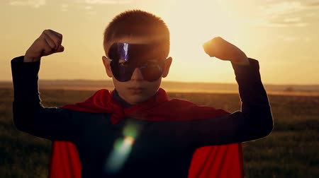 сильный : superhero boy running on the green field at sunset Стоковые видеозаписи