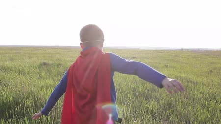 bravery : Boy dressed with a Superman cape running in a field, looking into the sunset