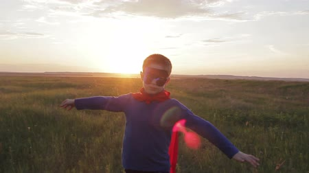 Boy dressed with a Superhero cape running in a field, looking into the sunset