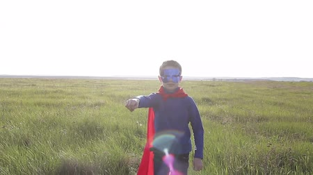 kahraman : Boy dressed with a Superman cape running in a field, looking into the sunset