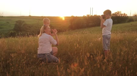 curto : Family is photographed in a field at sunset. Mother and two sons on vacation make selfie. Traveling on vacation