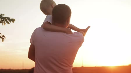 napsütéses napon : father and son having fun at sunset in a field looking at the sun Stock mozgókép