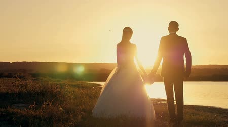 olhando a câmera : bride and groom running through the field to meet the sun at sunset, slow motion