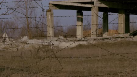genocide : Ruined buildings abroad from barbed wire refugees accommodation Stock Footage