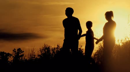 an : happy family at sunset silhouette of the water