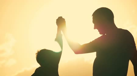 protesto : Father and son shake hands in agreement. Happy family having fun in the evening Beautiful nature landscape. Silhouettes of man and boy against the sky of sunset. Vídeos