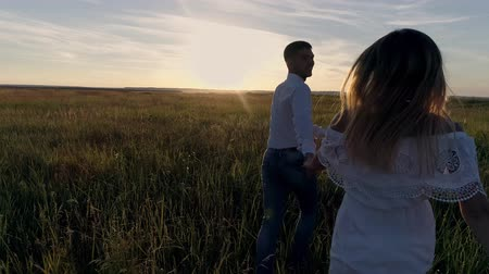 pólos : Young couple guy and girl running across the field towards the sunset. The concept of love. Slow motion Stock Footage