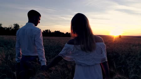 valentin nap : Young beautiful couple in a wheat field. Silhouette on sunset background. Slow motion Stock mozgókép