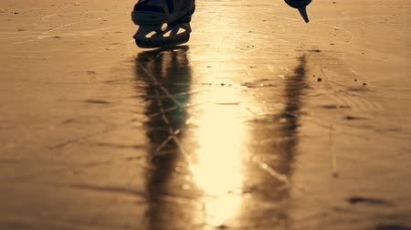 hockey rink : silhouette of a boy skating on ice on a lake in winter in the sun. Slow motion