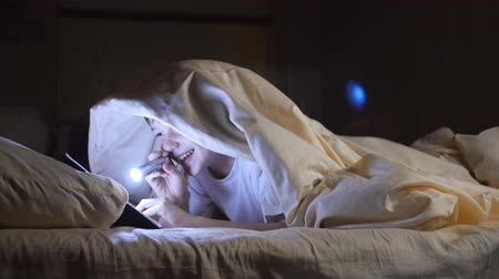 front cover : A child reads a book under blankets with a flashlight at night. Enthusiastic boy Stock Footage