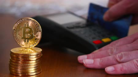 gênero alimentício : The womans hand is paid by a bank card using the terminal for payment on the background of gold coins of bitcoins. The concept of a new virtual crypto currency
