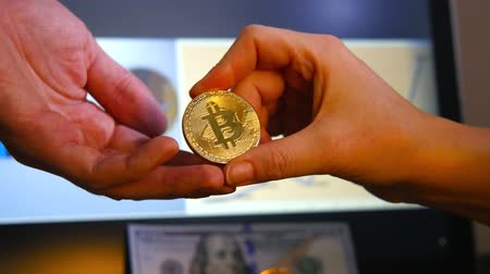 Close-up of a hand with a gold bitcoin against the background of the growth rate of the virtual currency rate. Transactions with crypto currency. The concept of a virtual exchange. Stock Footage