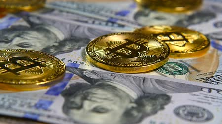 Gold coins of bitcoins and a background of hundred-dollar bills. The concept of financial operations. Economy of the future