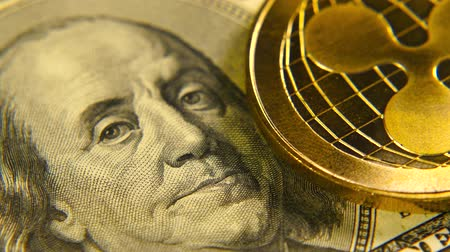 монета : Gold coins ripple is a market symbol of the crypto currency. A gold metal bitcoin over a paper currency.