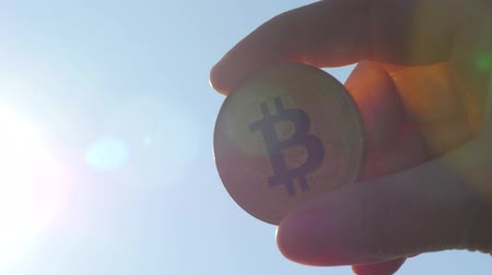 Silhouette Bitcoin in the hands glows in the rays of the sun