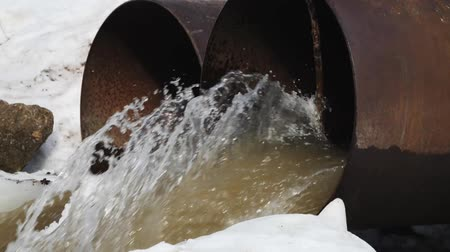 gushing : Dirty water flows out of the concrete pipe. Environmental pollution. Stock Footage