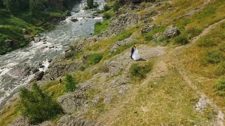 Beautiful Bride and groom wedding couple on a rock