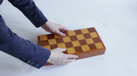 королева : The hand puts the chess box on the table and opens it.
