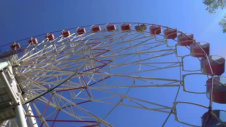 giant wheel : The Ferris wheel against the blue sky. Carousel in the Park. Stock Footage