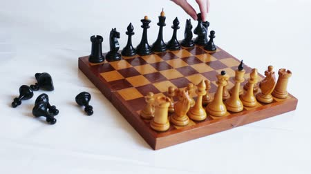cavaleiro : The hand puts the black pieces on the chessboard. Game of chess.