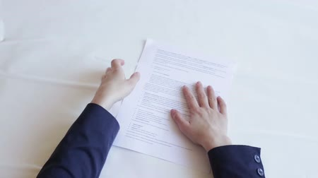 brasão : Man is angry. Tearing the document. White background. Woman hands in shot.