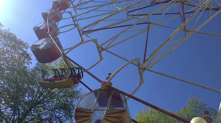 giant wheel : Ferris wheel against blue sky and trees. Sunny day. Park with attractions.