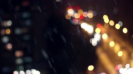 város : Snow flakes fall in bright light. Defocus city background