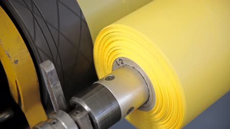 roll : Video shows a factory, producing plastic bags. Two shafts are rotating. Yellow cellophane is wrapping on a shaft.