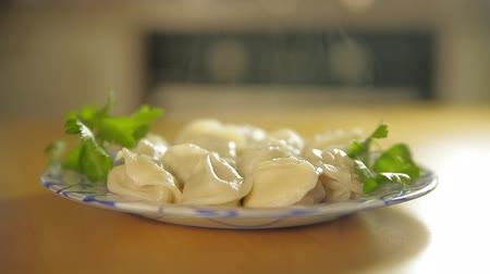 heilongjiang : Making of dumplings. A cook is putting a plate full of hot steaming dumplings on the table. Dumplings are decorated with greens. Stock Footage