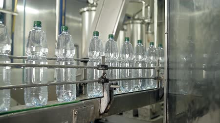 The machine is pouring mineral water into bottles