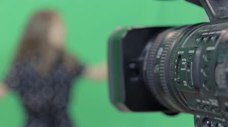 A girl is recording the program on a green background