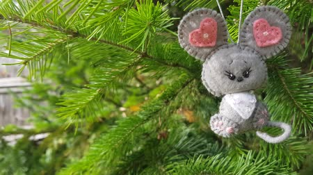 keçe : Christmas felt decoration on a spruce branch - close up. Handmade bauble figurines symbol of the year - mouse. Holiday video 4k background with a copy space.