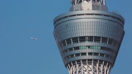 büyük yolcu uçağı : Tokyo Sky Tree close up with an airplane emerging from behind. Tokyo Sky Tree is the tallest tower in the world. Stok Video