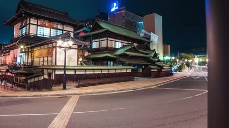 japan : Time lapse of the ancient Japanese bathhouse Dogo Onsen surrounded by car and foot traffic Stock Footage