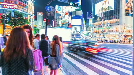 скрестив : People and vehicles cross the famous Shibuya intersection in Tokyo in time lapse on May 23, 2014.The Shibuya scramble crosswalk is one of the busiest intersections in the world.