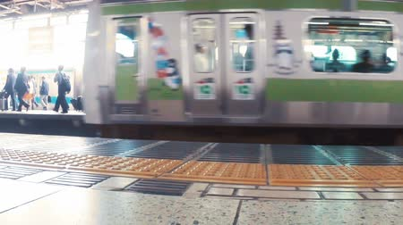 japonya : Slow motion subway car departs Daimon business district of Tokyo, revealing commuters walking on the other side. Shot with dedicated slow motion camera. Stok Video