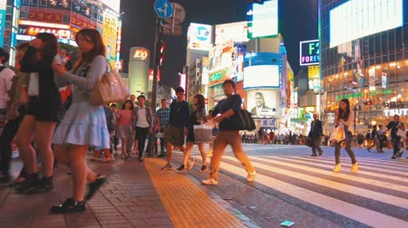 скрестив : People crossing the street outside the famously crowded Shibuya station, Tokyo, Japan.