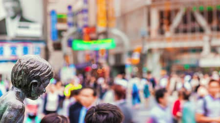gyalogos : Shibuya, Tokyo, Japan, motion time lapse of people and vehicles with blurred background and moving statue foreground.