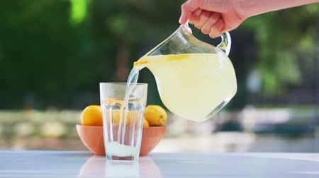 limonádé : Fresh lemonade pouring into a glass outside Stock mozgókép