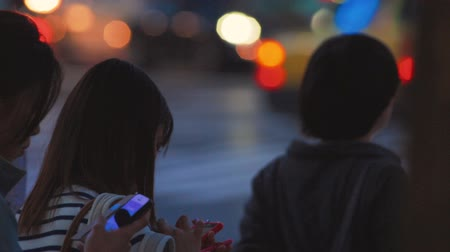telefone celular : Japanese woman checking her cellphone while waiting to cross the street outside the famously crowded Shibuya station, Tokyo, Japan. Stock Footage