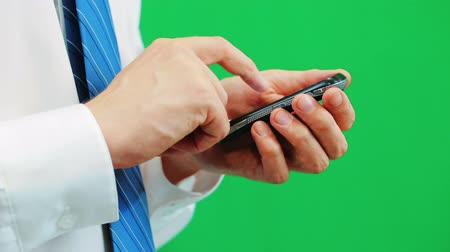 cellphone : Man using a cellphone isolated on green screen background