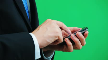 érintőképernyő : Man wearing a suit using a cellphone isolated on green screen background Stock mozgókép