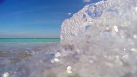 strand zand : Golven die over de camera in slow motion met audio Stockvideo