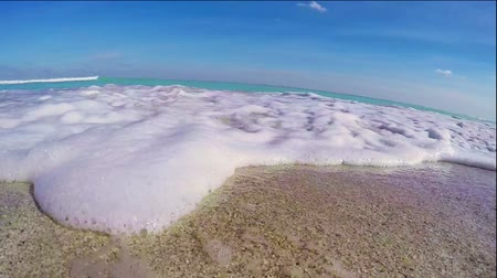 strand zand : Golven van de zee stroomt over de camera met audio Stockvideo
