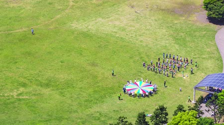 plac zabaw : Time-lapse of a large group of children playing in a field in Odaiba, Tokyo, Japan. Aerial shot.