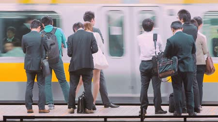 бизнес леди : People waiting to board trains at the subway station in Tokyo, Japan Стоковые видеозаписи